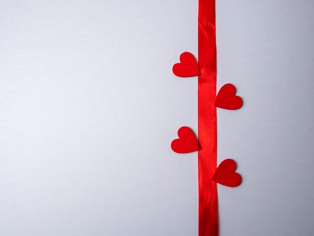 Fita longa vermelha cercada por quatro corações vermelhos em um fundo branco brilhante