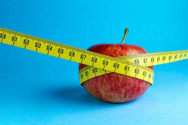 Fita métrica amarela e uma maçã