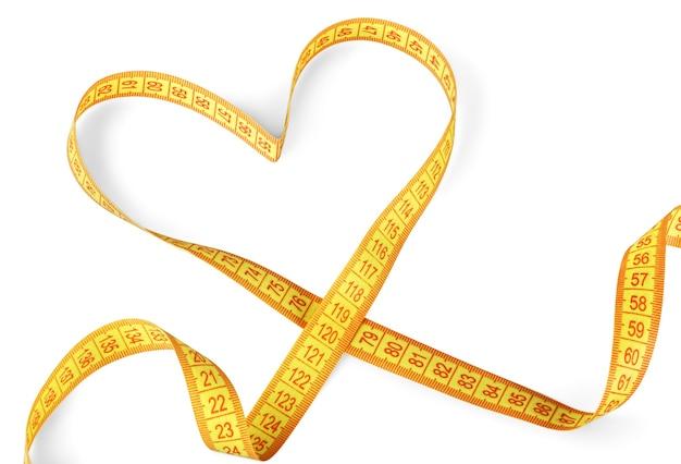 Fita métrica amarela em formato de coração isolada no fundo branco