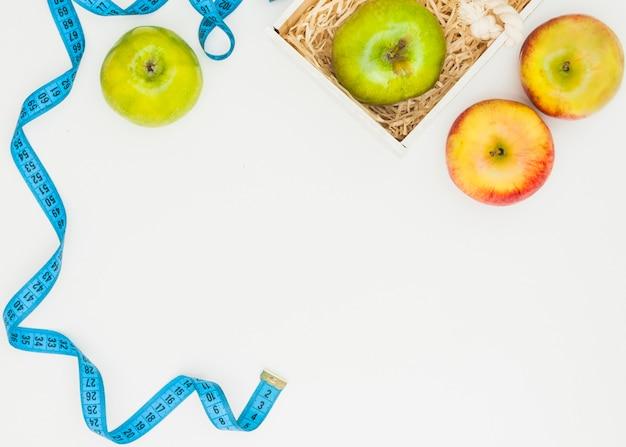 Fita métrica azul com maçãs verdes e vermelhas sobre fundo branco