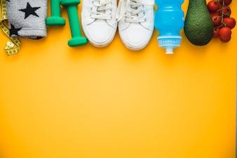 Fita métrica; braçadeira; halteres; sapatos; abacate de garrafa de água e tomate cereja em fundo amarelo