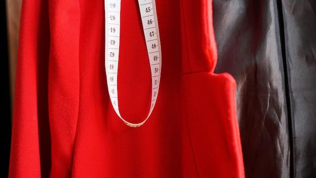Fita métrica branca no fundo do tecido vermelho da jaqueta. conceito de roupas de costura