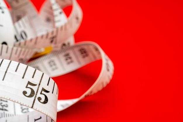 Fita métrica branca sobre fundo vermelho. medição de comprimento e circunferência. perder peso e engordar.