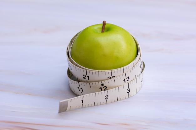 Fita métrica com maçã verde sobre fundo branco de mármore
