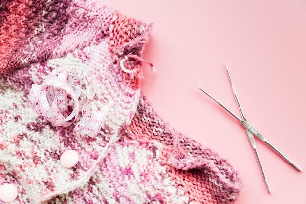 Fita métrica com tricô crochê e agulhas no pano de fundo rosa