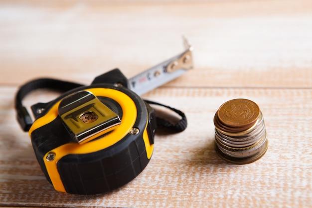 Fita métrica de construção e moedas na mesa