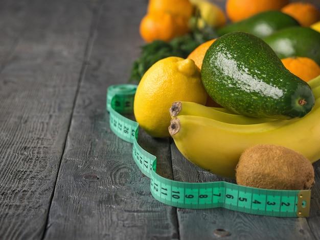 Fita métrica de cor verde com frutas tropicais em uma mesa de madeira.