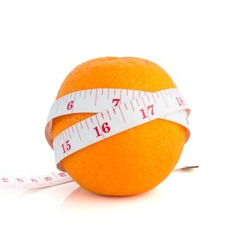 Fita métrica de corpo e laranja fresca em branco
