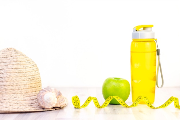 Fita métrica de lanche saudável sobre um fundo claro de madeira. preparação para a temporada de verão e o conceito de praia, conchas, perda de peso e esportes