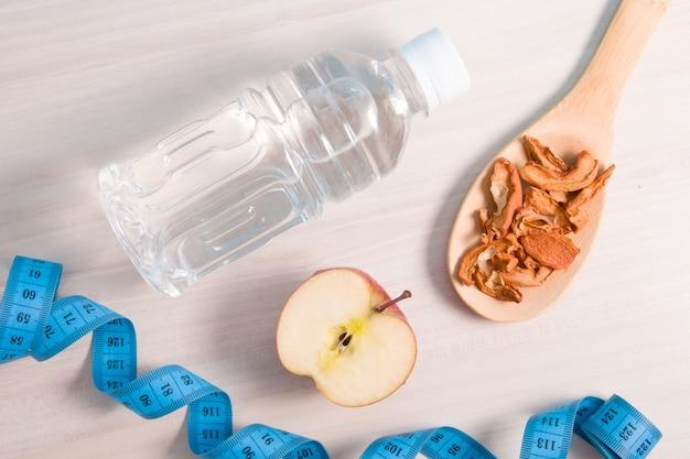 Fita métrica de maçã com frutas secas e água na mesa