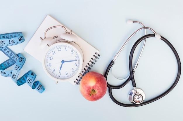 Fita métrica; despertador; bloco de notas em espiral; maçã e estetoscópio no fundo azul