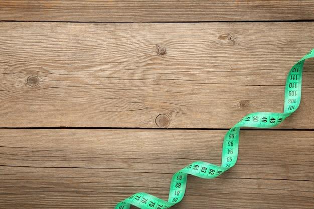 Fita métrica do alfaiate em um fundo de madeira