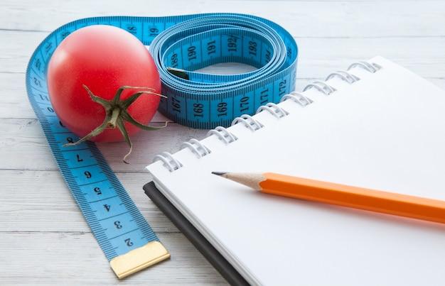 Fita métrica e caderno com tomates suculentos, o conceito de alimentação saudável e perda de peso