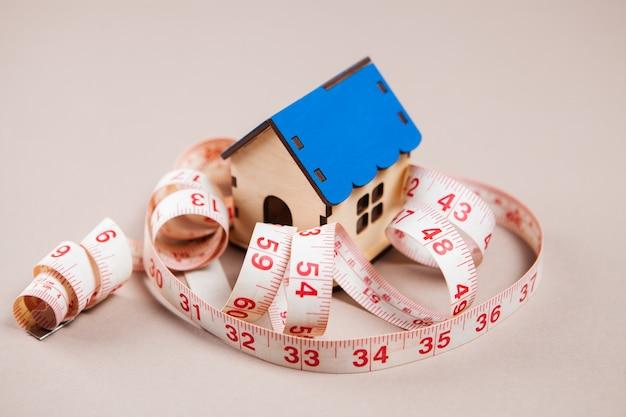 Fita métrica e casa na superfície branca