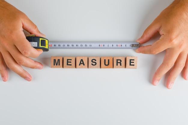 Fita métrica e cubos de madeira com a medida de texto