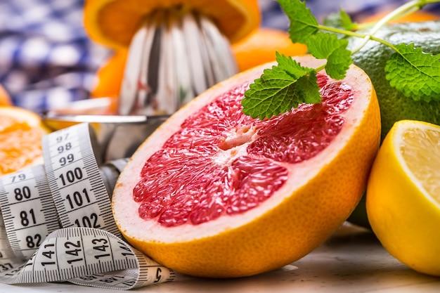 Fita métrica e frutas cítricas frescas laranja limão tangerina lima limão e toranja.