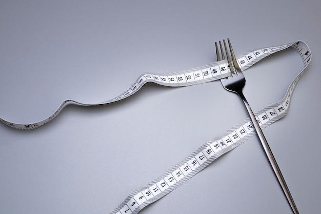 Fita métrica e garfo no fundo cinza nutrição adequada dieta médica da fome