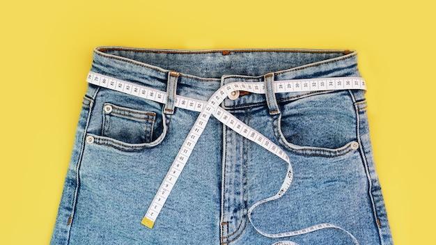 Fita métrica e jeans em um fundo amarelo brilhante. conceito de perda de peso no verão