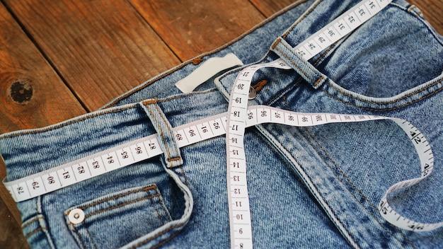 Fita métrica e jeans em um fundo de madeira. conceito de emagrecimento