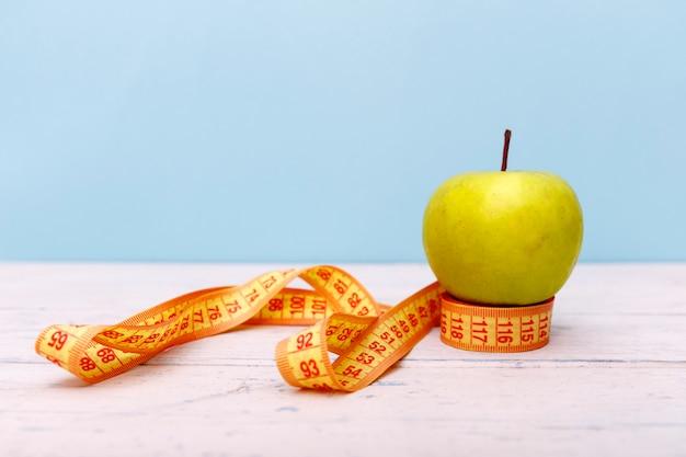 Fita métrica e maçã verde na mesa de madeira branca.