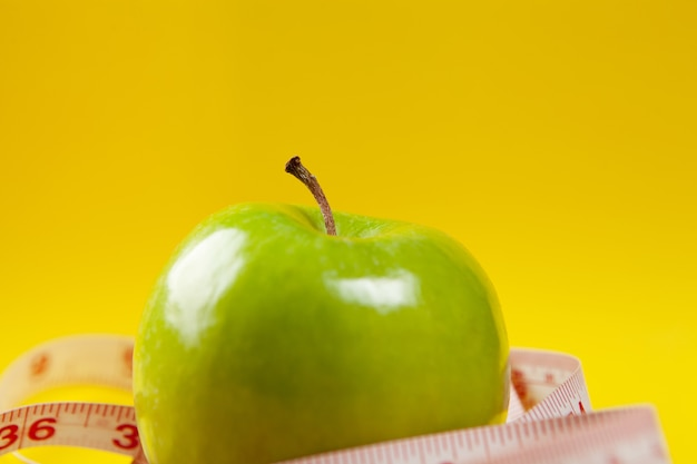Fita métrica e maçãs em um fundo amarelo