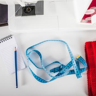 Fita métrica e notebook perto da máquina de costura