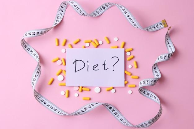 Fita métrica e pílulas dietéticas em um plano de fundo colorido, close-up