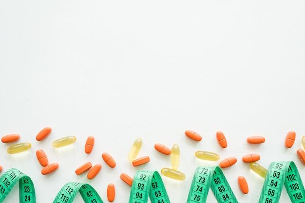 Fita métrica e pílulas dietéticas. emagrecimento e vício. drogas em branco