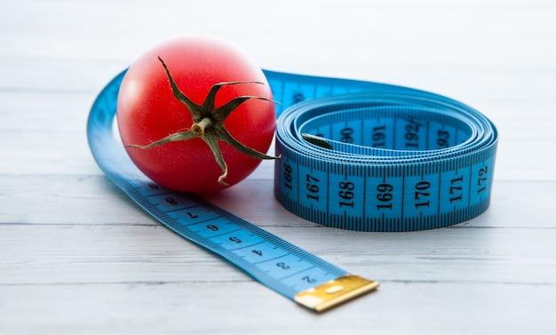 Fita métrica e tomate suculento, o conceito de nutrição saudável e perda de peso