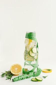 Fita métrica e uma garrafa de água infundida com limão, pepino e alecrim. conceito de dieta e queima de gordura