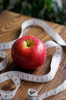 Fita métrica e uma maçã vermelha em uma mesa de madeira. planta verde. o conceito de dieta, estilo de vida saudável e nutrição adequada.
