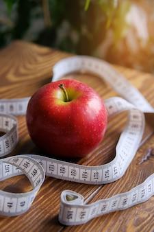 Fita métrica e uma maçã vermelha em uma mesa de madeira.