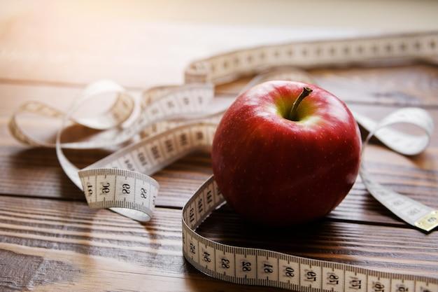 Fita métrica e vermelho maçã no fundo de madeira