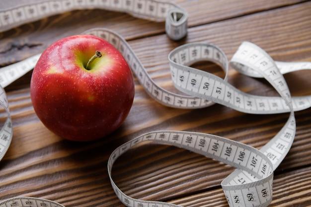 Fita métrica e vermelho maçã. o conceito de dieta, estilo de vida saudável e nutrição adequada. fechar-se.