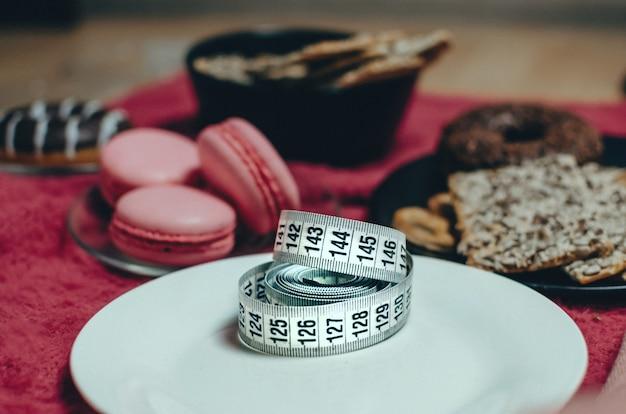 Fita métrica em chapa branca perto de doces e pastelaria