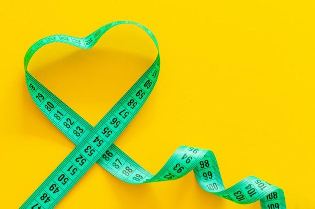 Fita métrica em forma de coração em fundo amarelo