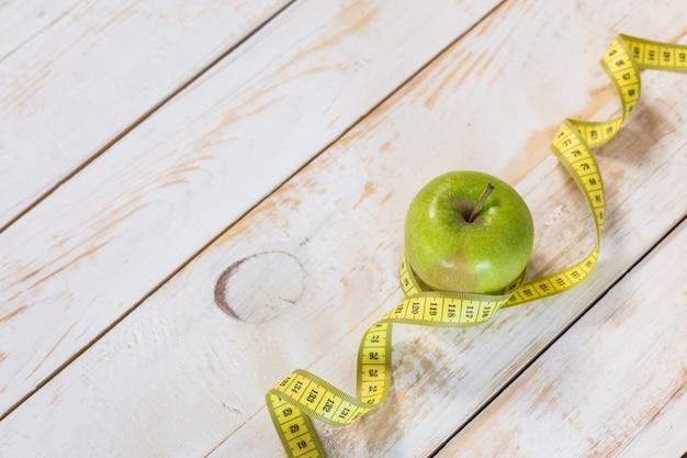 Fita métrica em um fundo de madeira. conceito de dieta