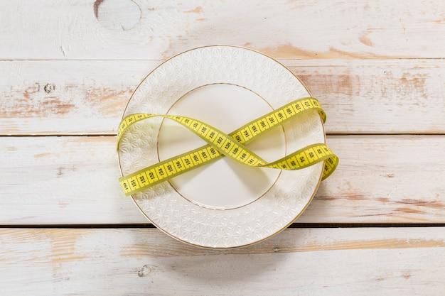 Fita métrica em um fundo de madeira. dieta