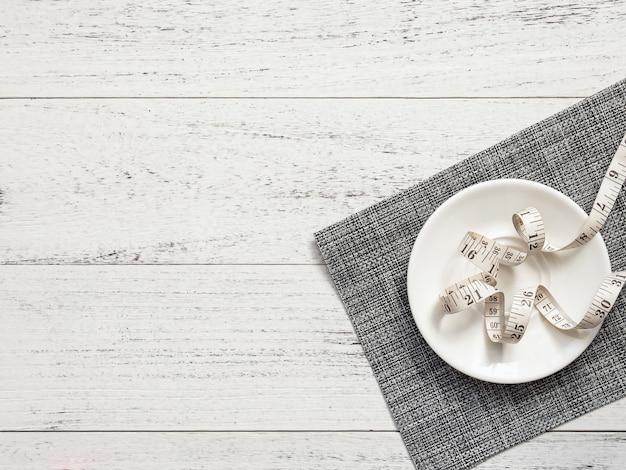 Fita métrica em um prato branco sobre uma mesa de madeira branca, vista superior.