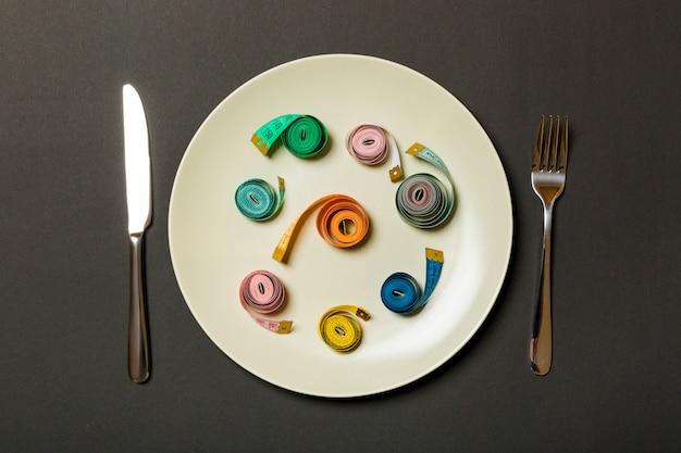 Fita métrica em um prato com garfo e faca