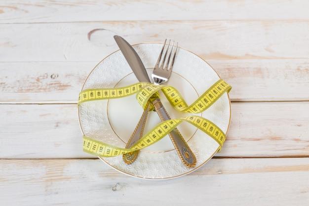 Fita métrica em uma mesa de madeira. conceito de dieta