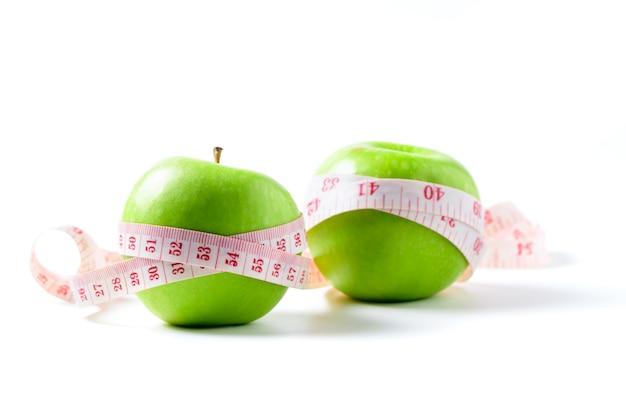 Fita métrica enrolada em torno de duas maçãs verdes isoladas no fundo branco, conceito da meta de perder peso, a meta da dieta
