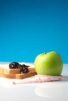 Fita métrica enrolada em uma maçã verde com uma fatia de pão branco