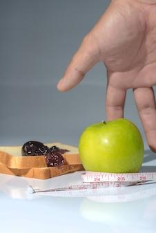 Fita métrica envolvida em torno de uma maçã verde