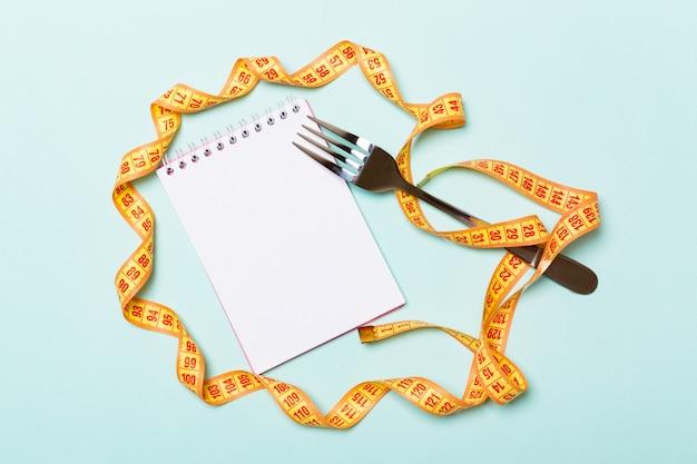 Fita métrica laranja, notebook aberto e garfo