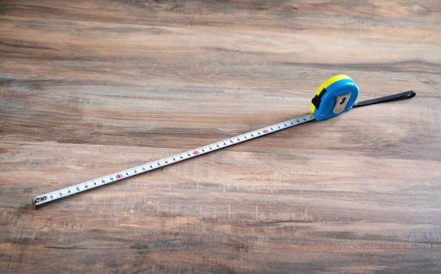 Fita métrica na mesa de madeira.
