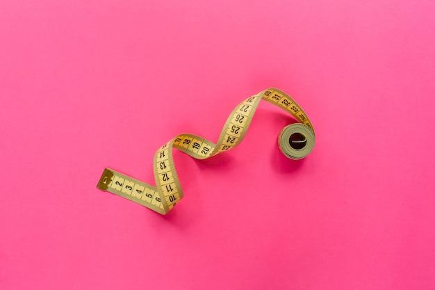 Fita métrica na superfície rosa