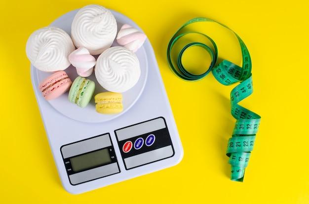 Fita métrica verde, balança de cozinha digital com macarons e merengues em amarelo