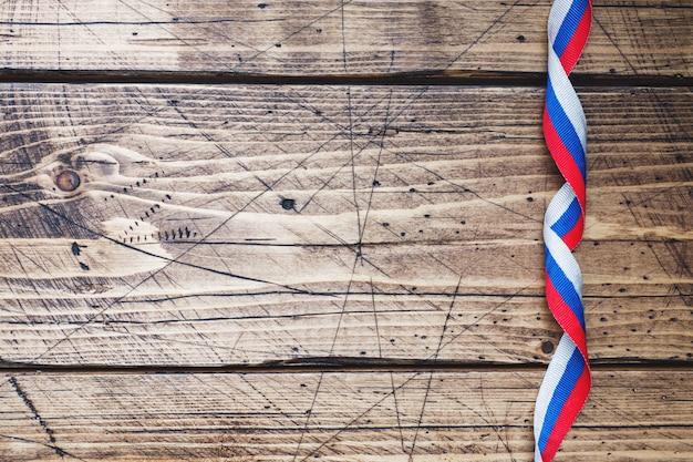Fita nas cores da bandeira russa tricolor no espaço da cópia de fundo de madeira
