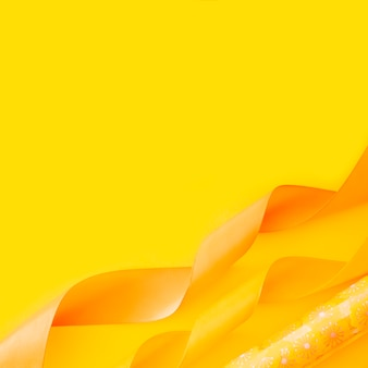 Fita ondulada decorativa e papel de presente sobre fundo amarelo